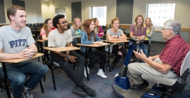 Person in electric wheelchair giving presentation to students sitting at desks